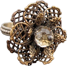 'Flower Ring 4' is created by the artist Beate Nyfløt. The stone is faceted swarovski crystal bead. The decor is oxidized brass filigree. The ring is 525 sterling silver.