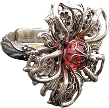 'Flower Ring 6' is created by the artist Beate Nyfløt. The stone is faceted swarovski crystal bead. The decor is silver plated brass filigree. The ring is 525 sterling silver.