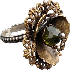 'Flower Ring 7' is created by the artist Beate Nyfløt. The stone is faceted swarovski crystal bead. The decor is oxidized brass filigree. The ring is 525 sterling silver.