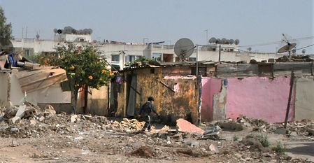 Boy walking through rubble of shantytown in Morocco