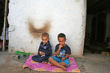 Children sitting outside of their home in Sidi Moumen