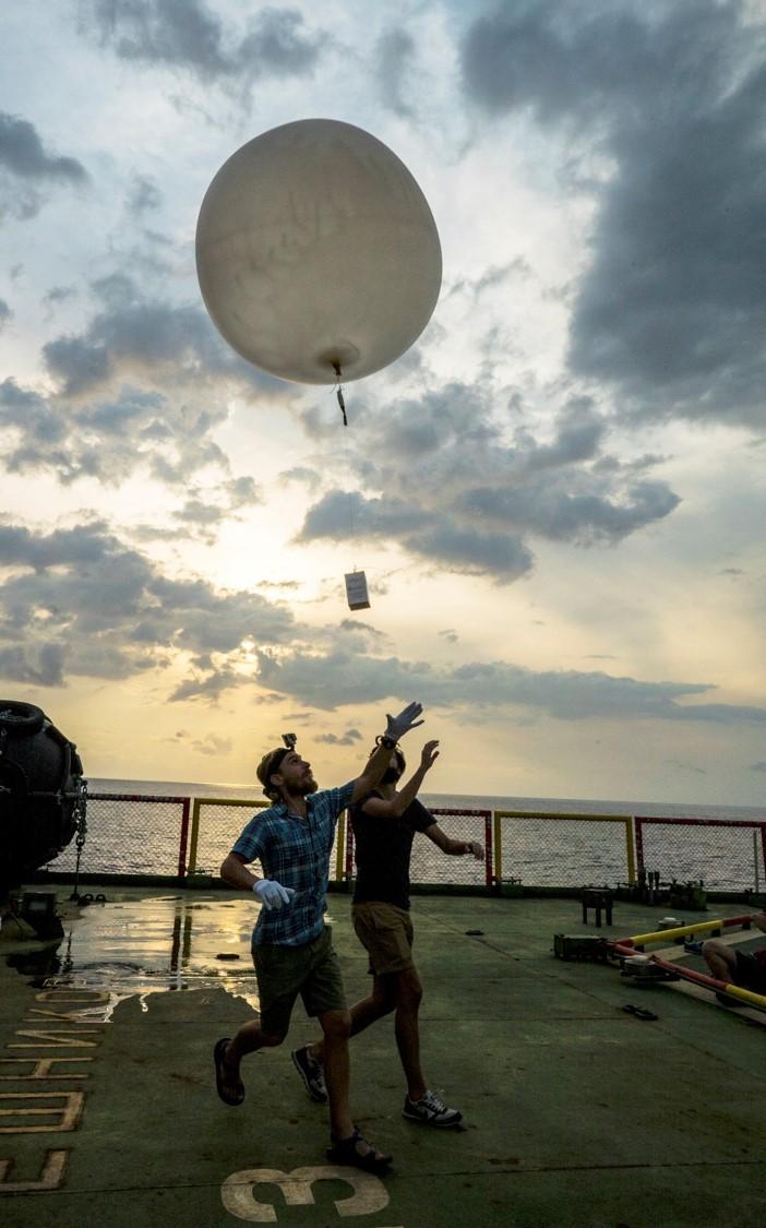 Releasing a radiosonde balloon to take atmospheric measurements