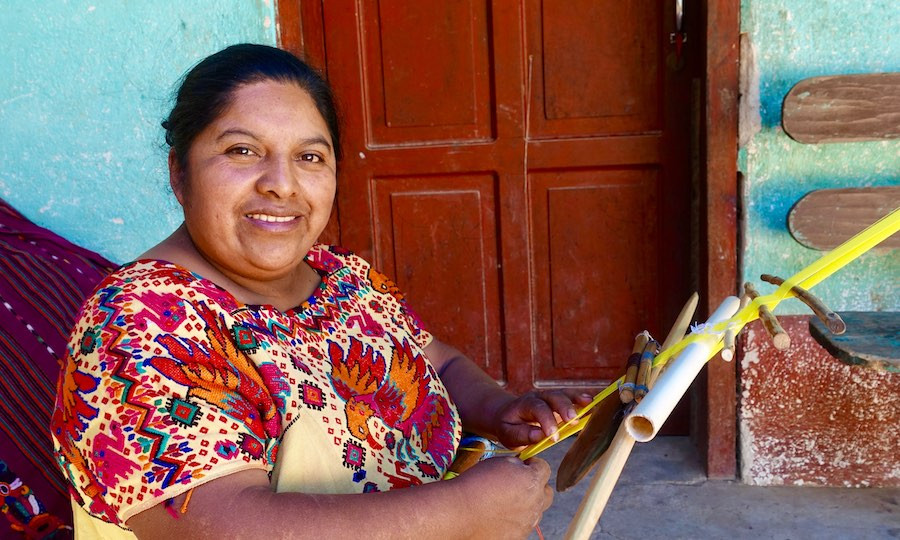 Indigenous Guatemalan artisan weaves on back strap loom