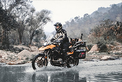 Greg Stone and German Shepherd Moxie ride across a small river on their BMW G650GS motorcycle