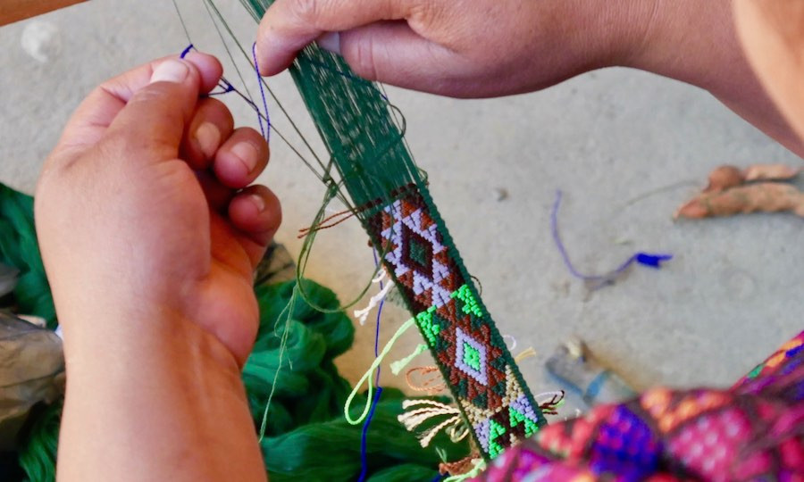 Indigenous Guatemalan artisan woman weaves típico ribbon on back strap loom