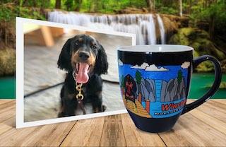 Black dog on photo beside engraved, painted mug with same image on natural background