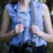 Woman wearing colorful macrame camera strap on blue handwoven fabric