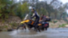 Man rides BMW motorcycle across river with German Shepherd laying in motorcycle dog carrier