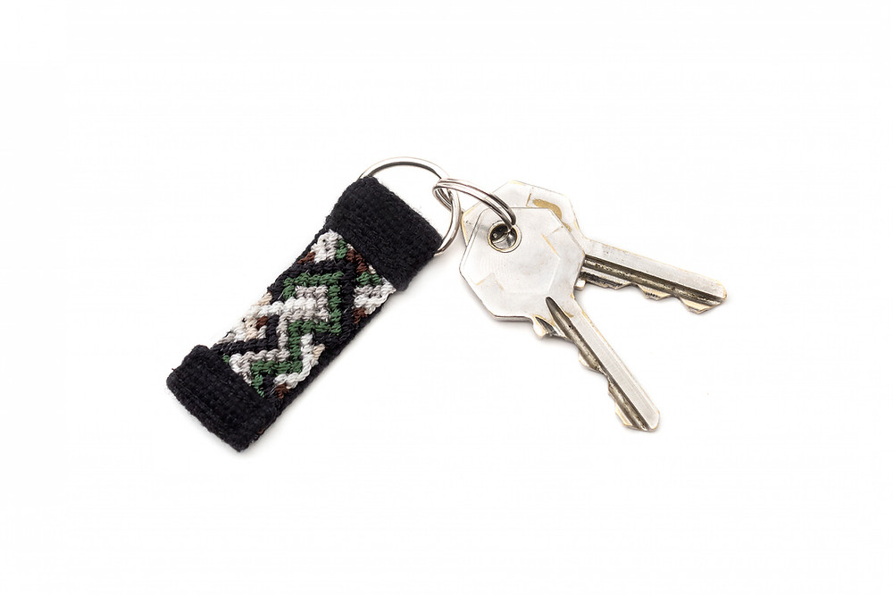 green and brown keychain with two keys attached