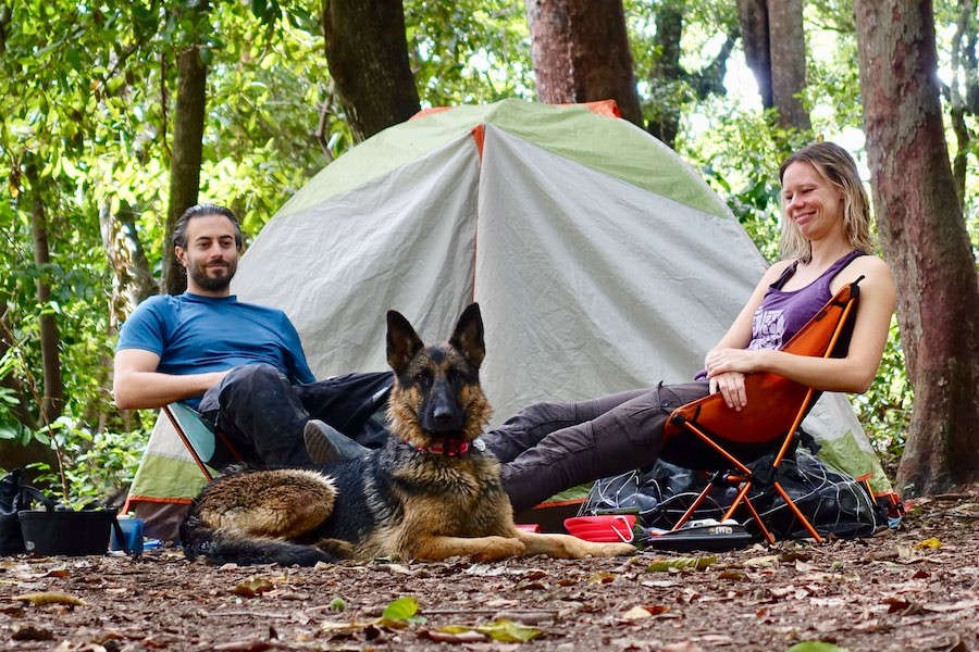 A couple and dog sit beside tent at campsite in the woods