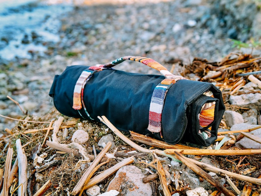 Handmade, waterproof dog travel bed rolled up with matching carry strap handle