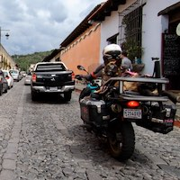 Woman and dog ride BMW motorcycle on bad Antigua Guatemala cobblestones