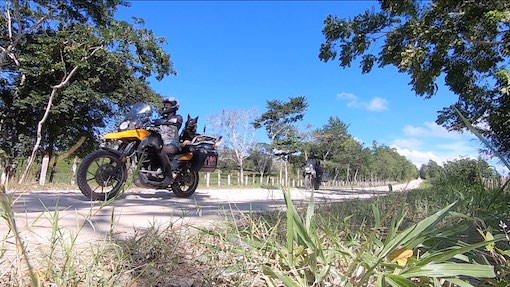 Woman and German Shepherd dog ride motorcycle followed by another BMW motorcycle on dirt road