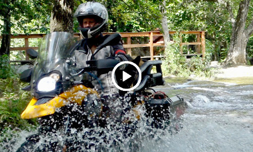 Woman and German Shepherd dog on BMW motorcycle ride through river