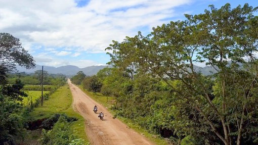 Two BMW motorcycles drive along dirt road