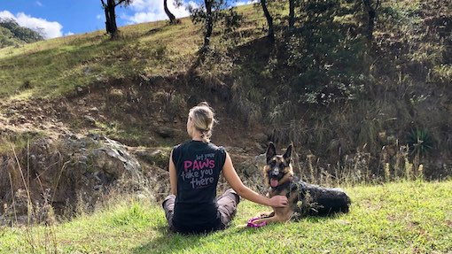 Woman wearing Let Your Paws Take You There shirt sits on grassy hill with German Shepherd dog