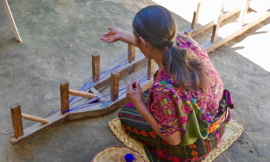 Indigenous artisan woman prepares típico thread for weaving