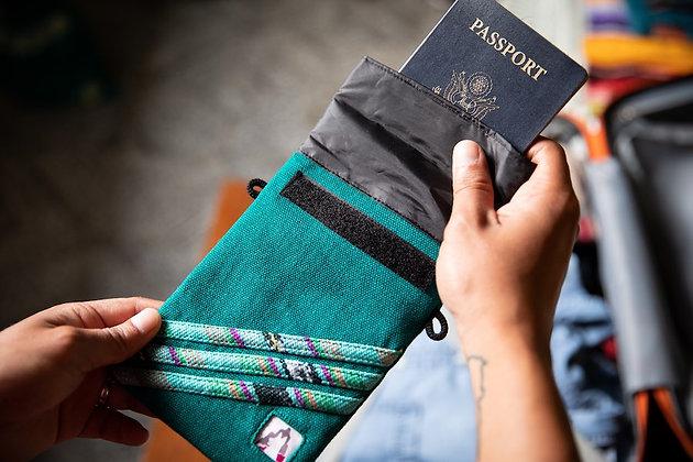 Hands retrieve an American passport from a jade green handmade waterproof passport pouch