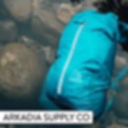 Jade green waterproof Sea to Sky Pack by Arkadia Supply Co partially submerged in river