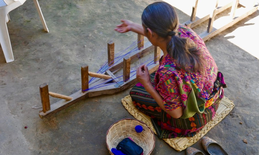 indigenous Guatemalan artisan sits on ground to weave