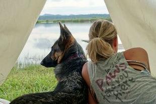 Woman lies beside German Shepherd dog inside tent looking out on lake scene