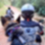 woman rides motorcycle with German Shepherd dog and man ride motorcycle ahead on dirt road