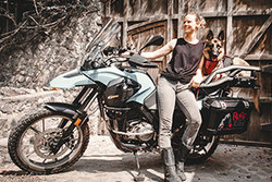 : Jess Stone and German Shepherd Moxie pose for a photo with their K9 Moto Cockpit motorcycle dog carrier