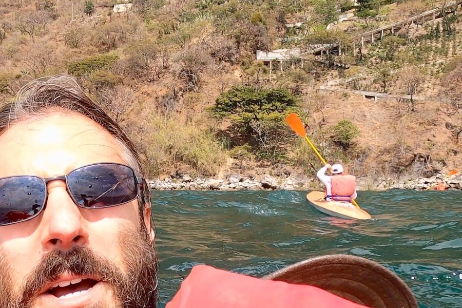 Man treads water in lake beside kayaker
