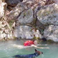 Woman and dog swim in river beside cliff