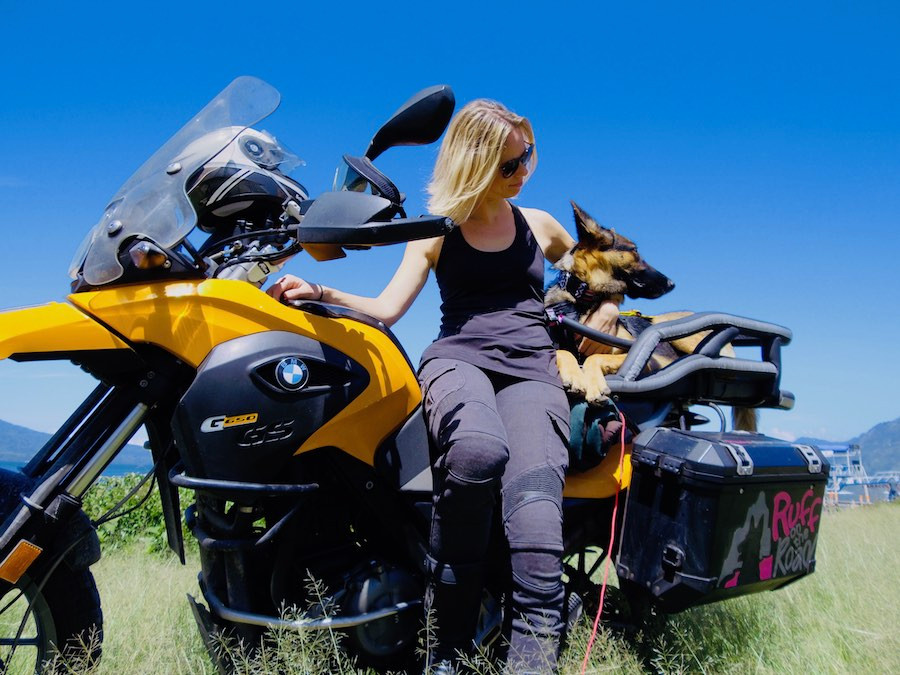 Woman leans against motorcycle with dog in carrier