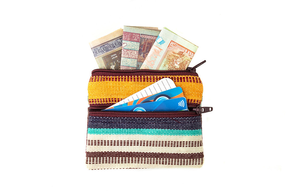 Change purse with two zippered compartments open with money and credit cards sticking out