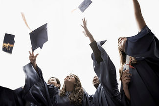 Stock photo of a group of graduates in gowns throwing caps in air