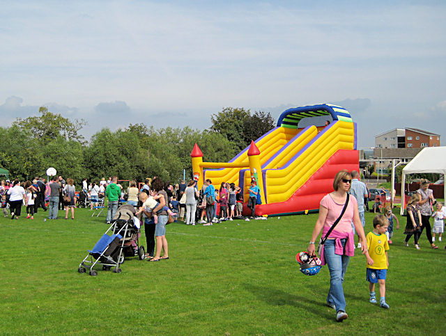 community event in a park with an inflatable slide and families
