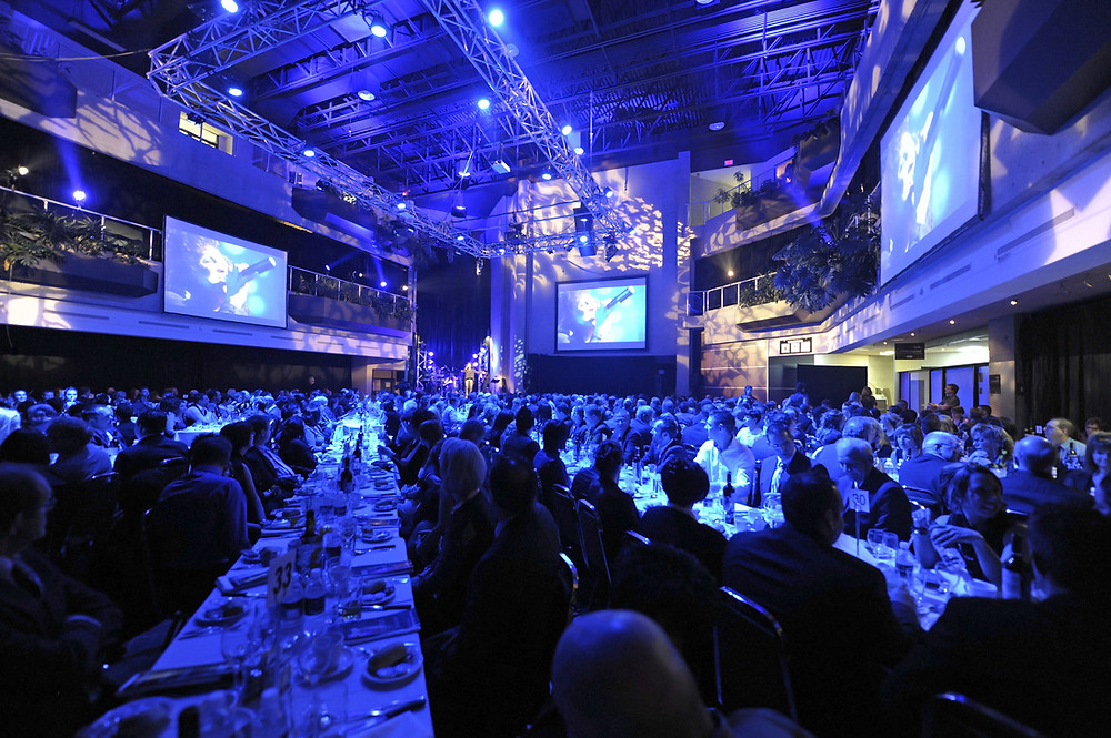 high-end gala event; hundreds of people seated at decorated tables watching a video on stage