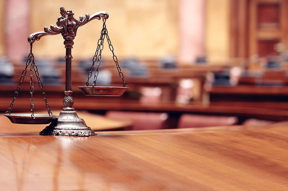 justice scales sitting on wooden desk