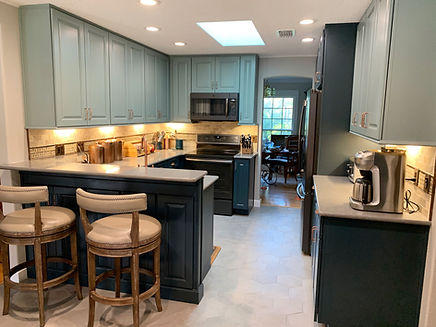 This kitchen remodel features a french country theme with soffit removal, brass hardware and blue cabinets.