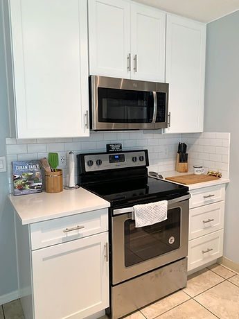 Updated range area with microwave and white backsplash