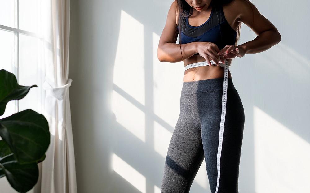 Asian woman measuring waist size