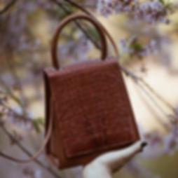 Bolsa feita em couro com árvore cerejeira atrás