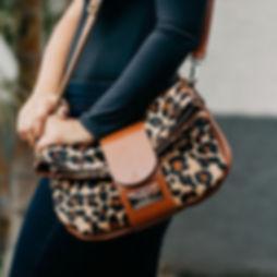 modelo vstida e preto com bolsa de couro com estampa de leopardo
