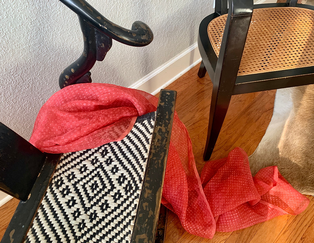 An abstracted view of two chairs showing textures of a black lacquer Chinese Emperors Folding Chair with patterned woven seat, a crimson silk scarf, and a vintage black lacquer Dunbar-Wormley chair with woven cane seat.
