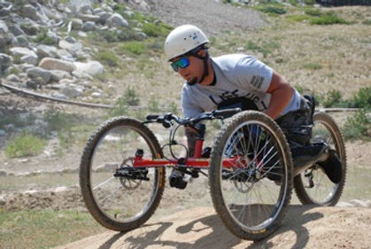 Adaptive sports participant using arm-powered mountain bike.