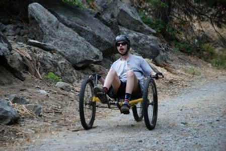 Adaptive sports participant in recumbent mountain bike.