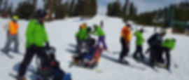 Numerous instructors with adaptive sports participants in sit-skis.