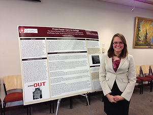 Photo of Angela Hoffman in black skirt and beige blazer standing next to poster titled From Foster Care to College.