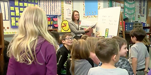 Photo of Angela Hoffman reading a book to a class of young children.