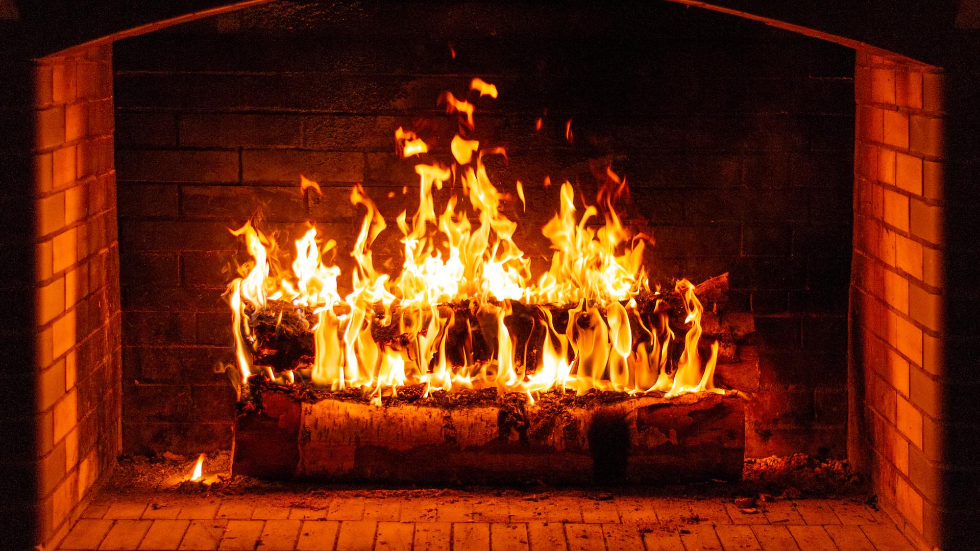 Glowing fire in a huge stone fireplace.j