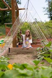 A girl camper digging in the garden