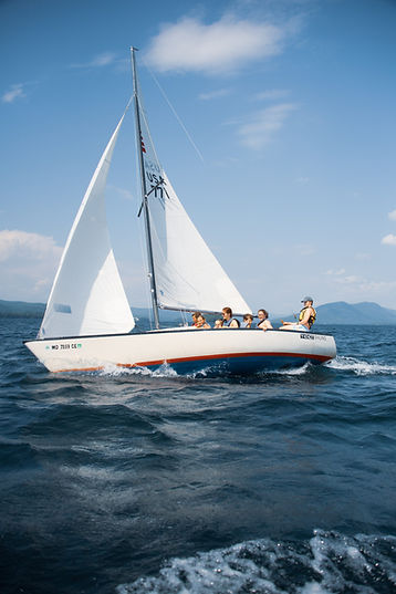 group of teens sailing a large boat on Lake George on a sunny day
