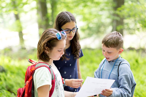 2 girls and 1 boy reading a book in nature